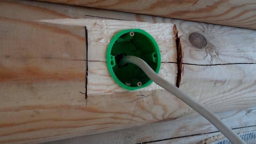 Пластиковый подрозетник довольно удобен для деревянной стены
