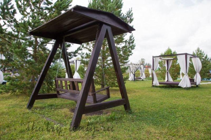 Деревянные садовые качели в парке
