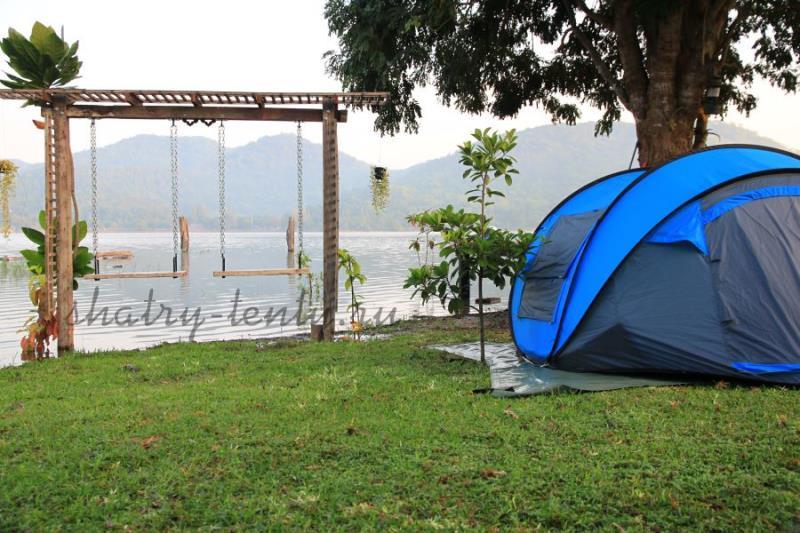 Подвесные деревянные качели на берегу озера