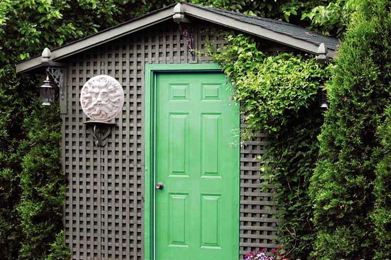 Дачный сарайчик, скрытый в глубине сада за вертикальным озеленением