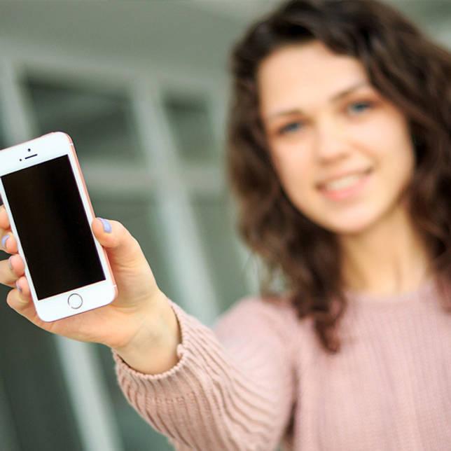 девушка показывает телефон