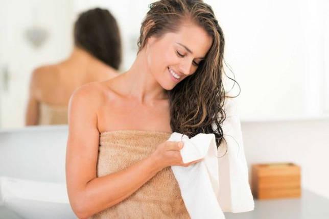 Девушка вытирает волосы полотенцем