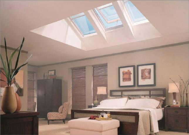 Мансардные окна обеспечивают много света в этой спальне
